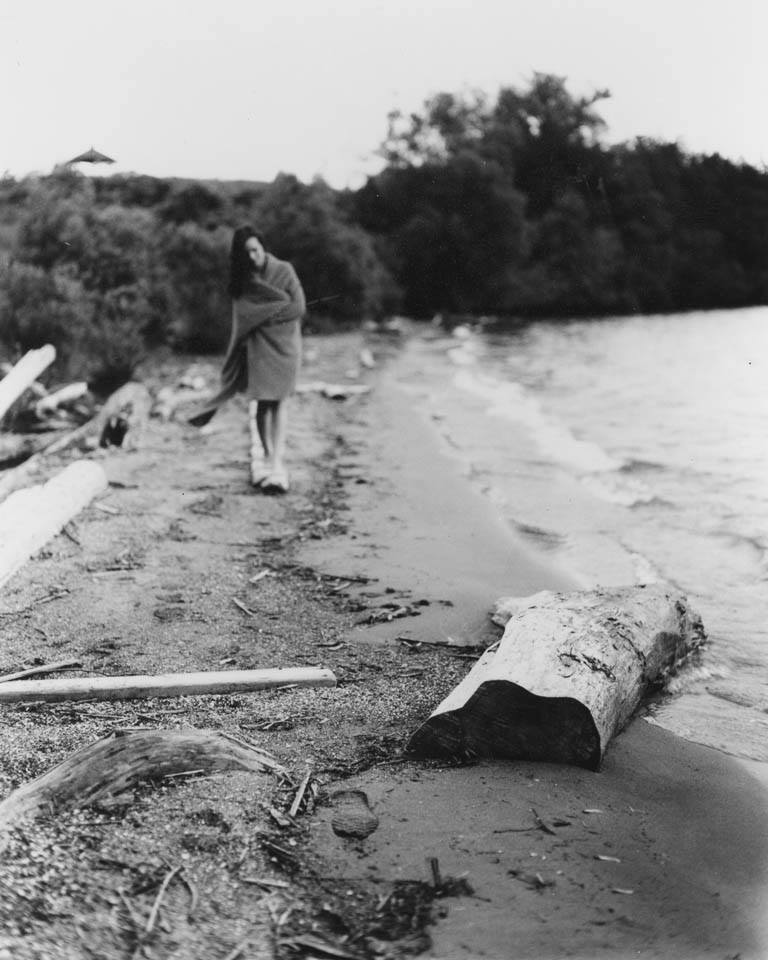 A 4x5 film portrait of a girl on a beach with driftwood