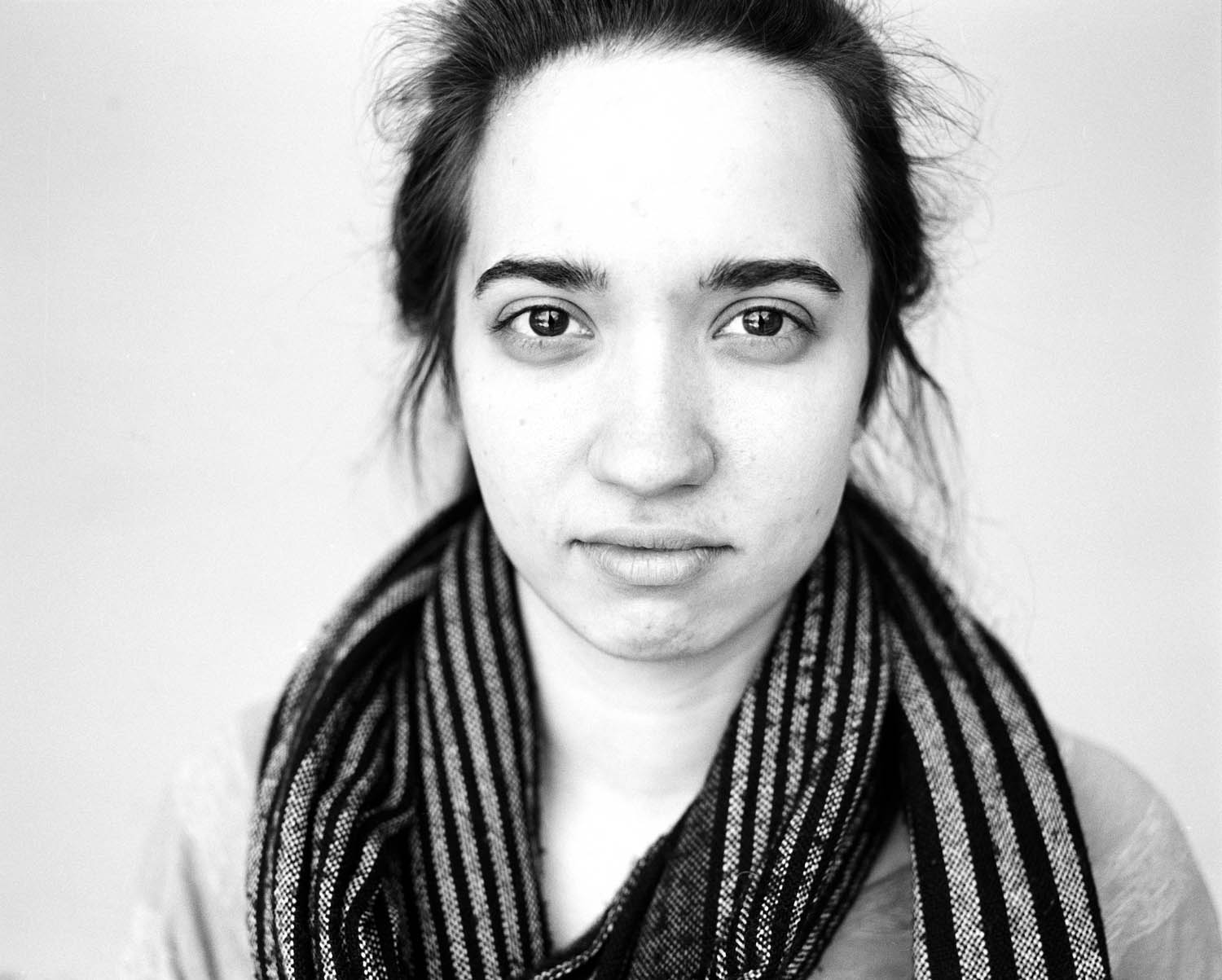 Black and white headshot portrait of a girl against a white background. Photographed with a Mamiya RB67