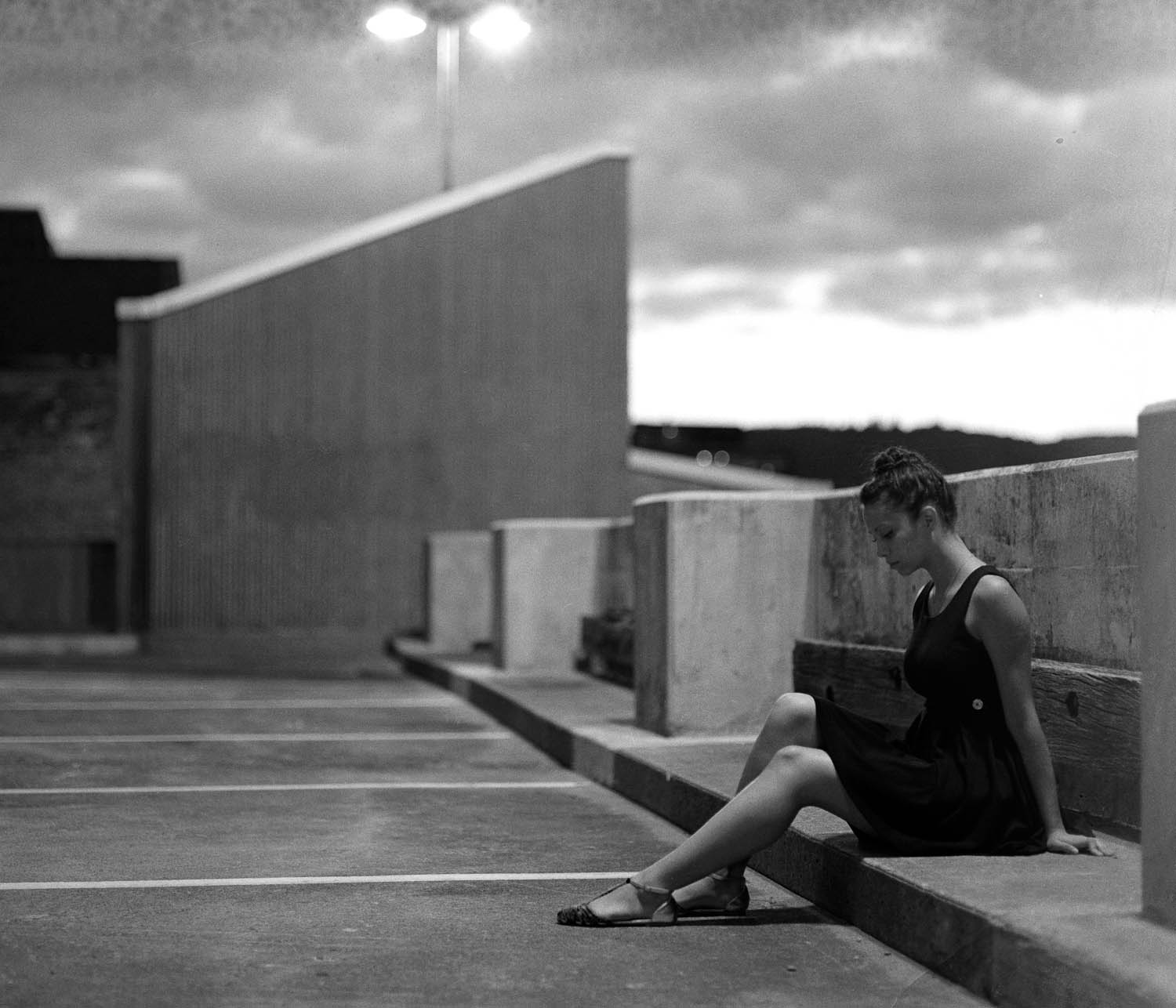 Black and white photograph of a girl sitting on a rooftop, photographed with a Pentax 67