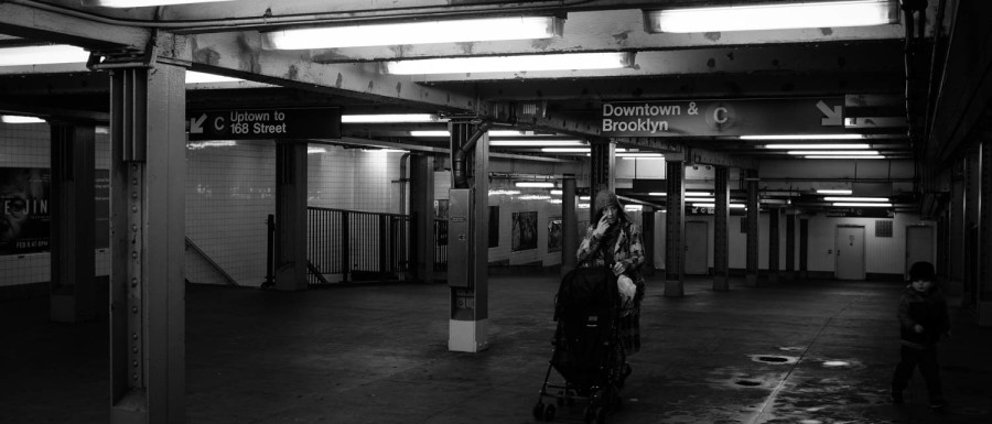 A black and white photograph of a woman pushing a stroller through a New York City subway station.