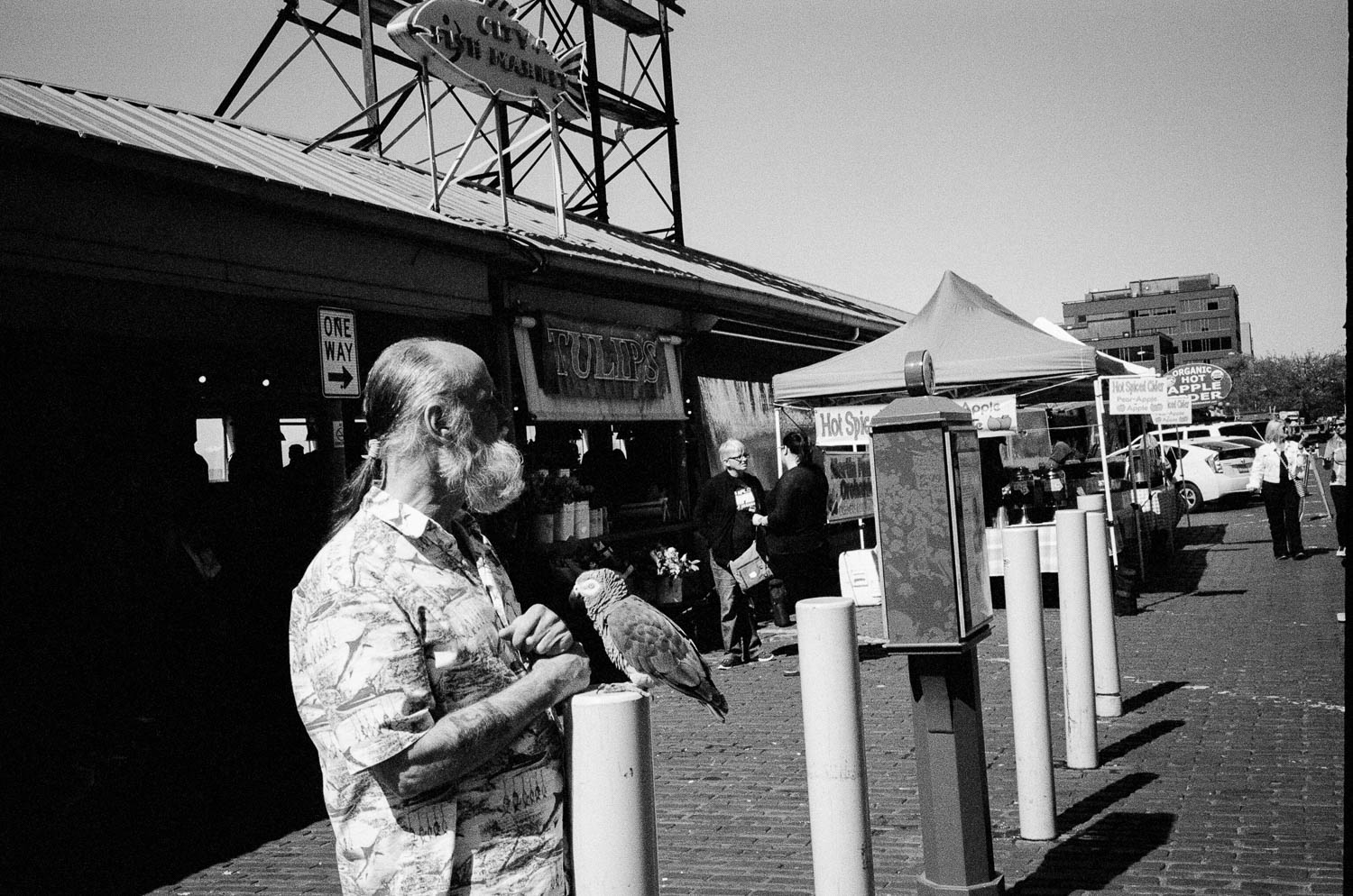 A man with a parrot in front of Pike Place Market in Seattle