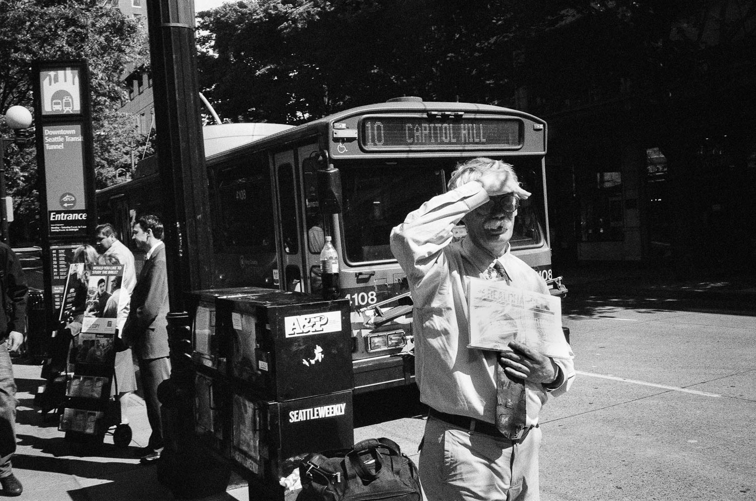 A Seattle man shielding his eyes from the sun while holding a newspaper in front of a city bus