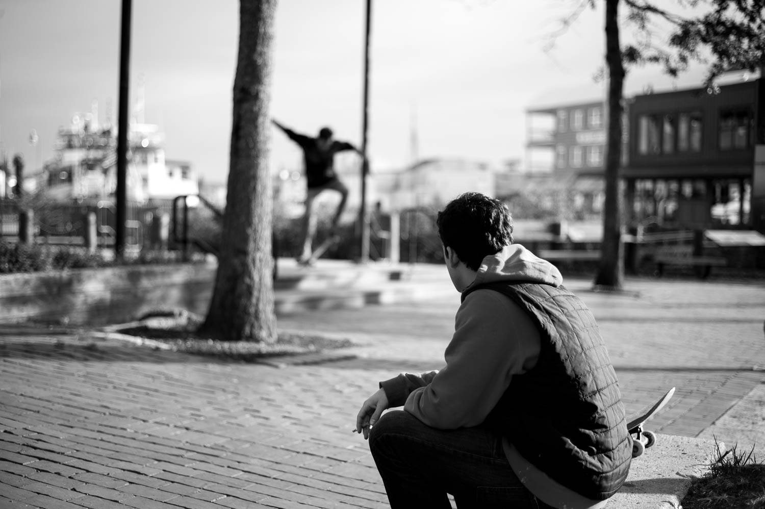 A skateboarder smoking a cigarette with his friend skateboarding in the background behind him