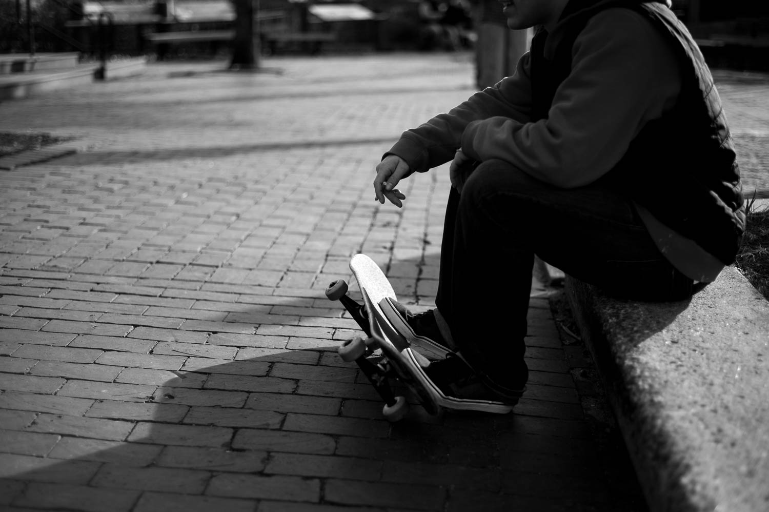 A black and white photo of a skateboarder smoking a cigarette