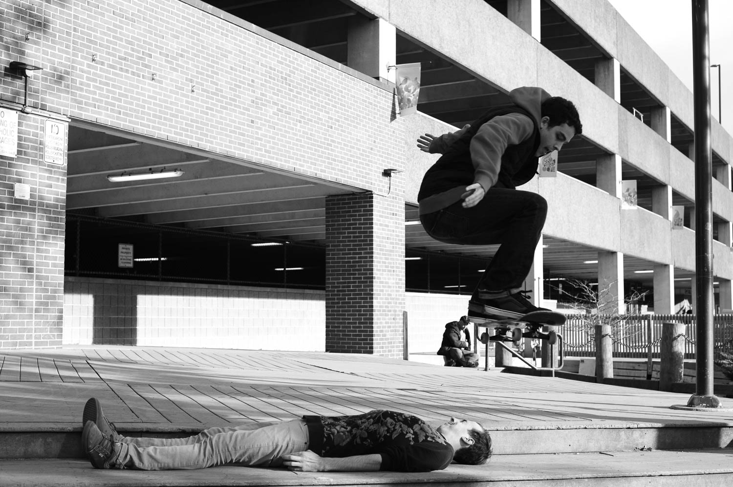 A skateboarder suspended in air above his friend, who is lying down and squinting