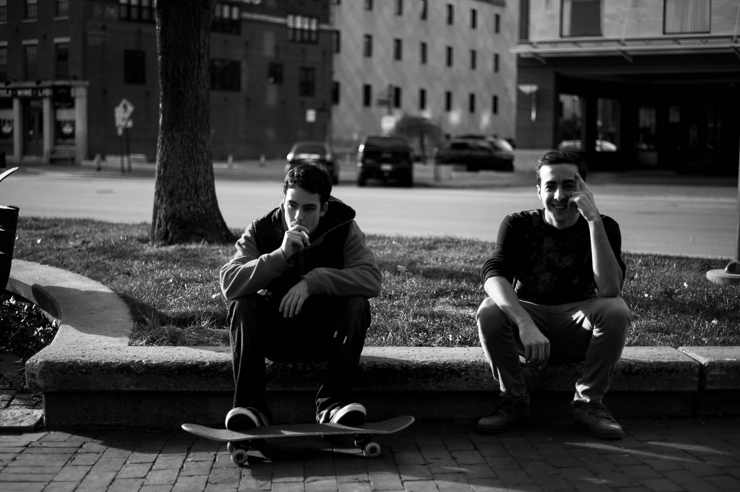 Two skateboarders hanging out and smoking cigarettes