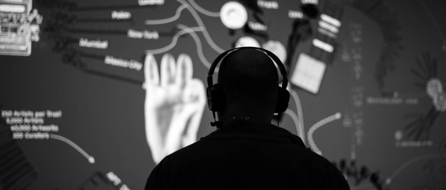 A man wearing headphones and looking at an interactive display at ICA Boston