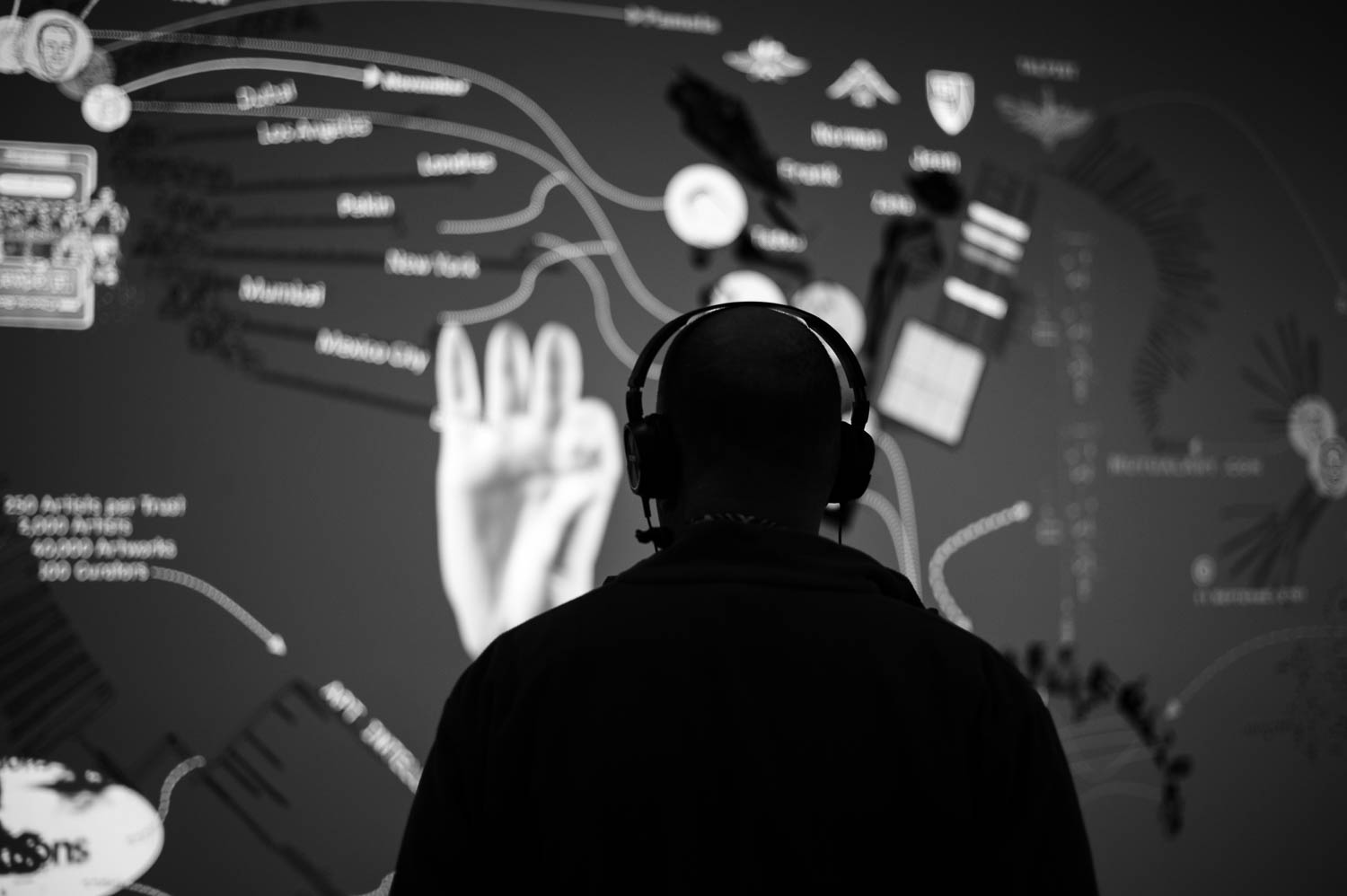 A man wearing headphones and looking at an animated display at ICA Boston