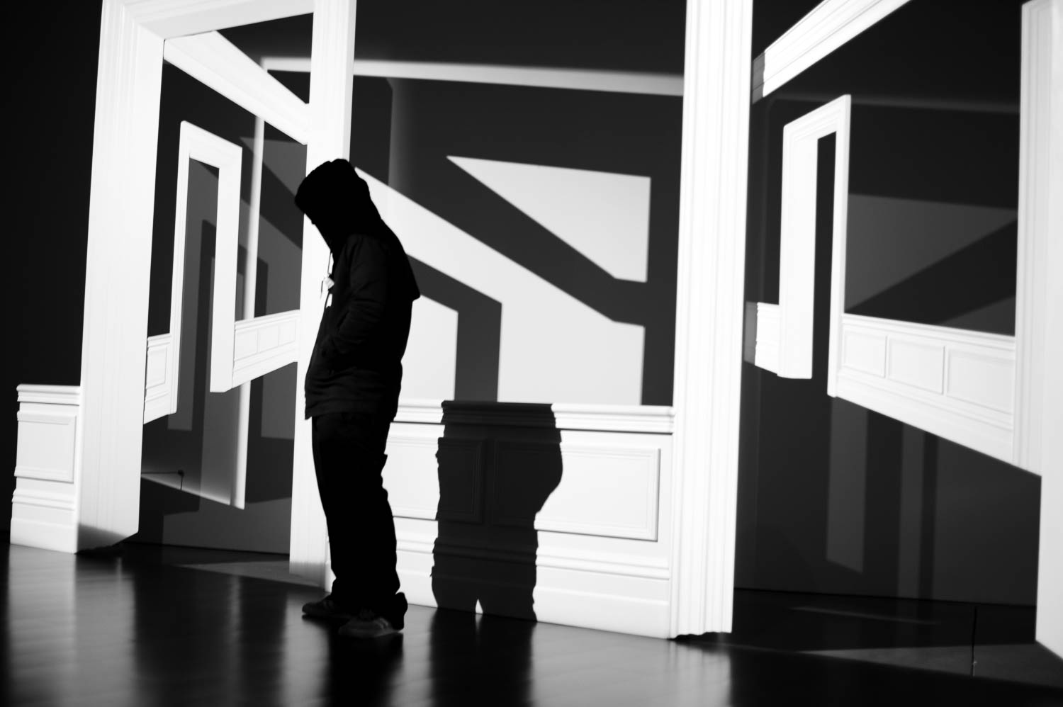A figure stands in front of an art exhibit at ICA Boston with harsh shadows