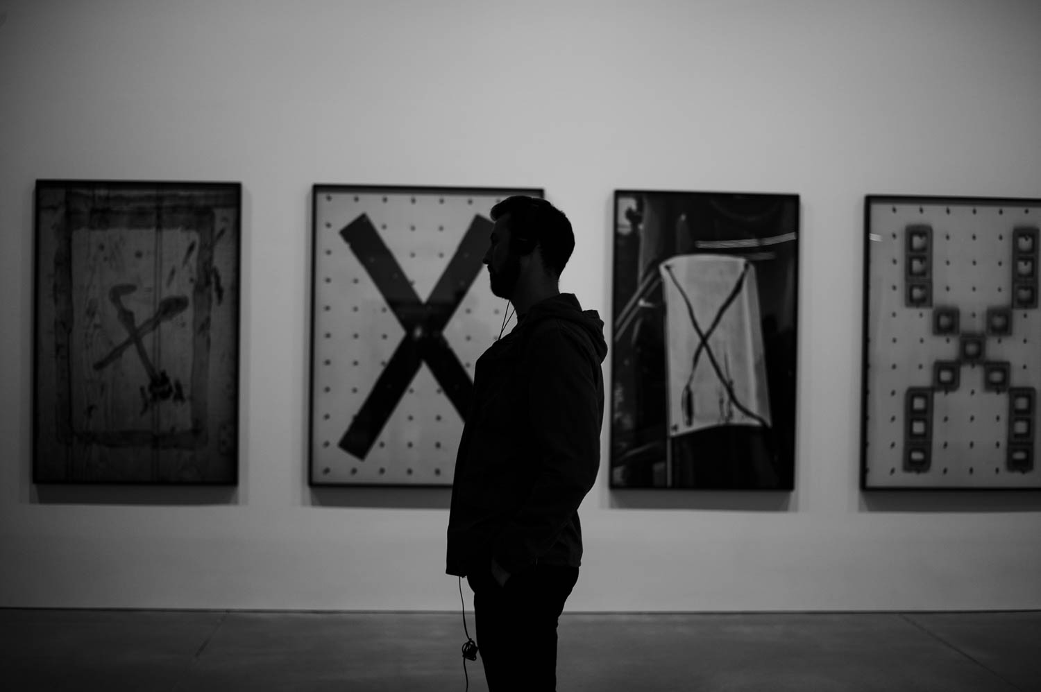 A man standing in front of four large prints of photographs of X-shapes