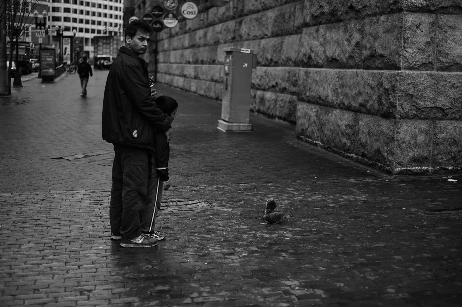A man and his son feed pigeons in Boston