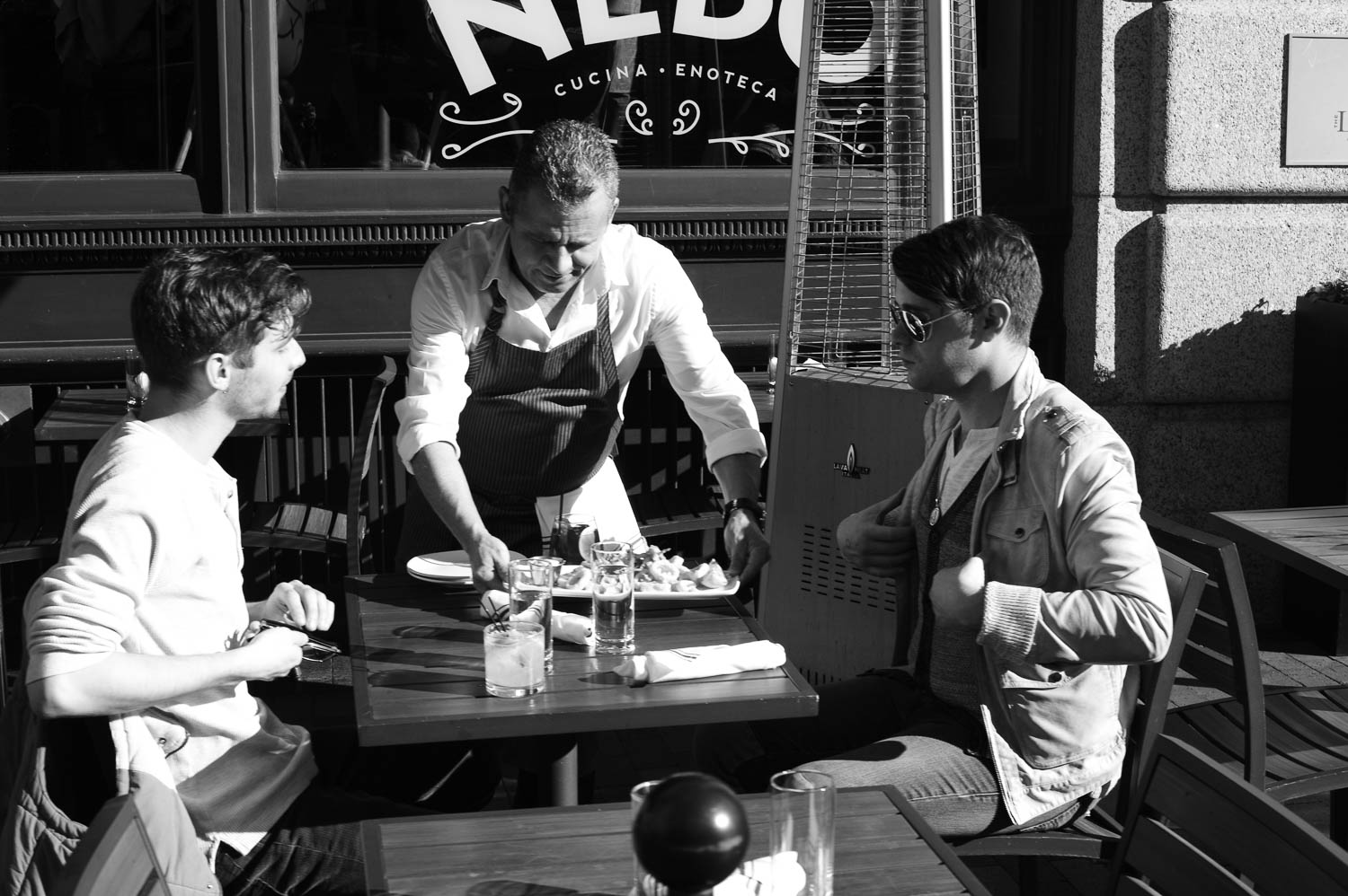 A waiter serves two men at an outdoor table in Boston
