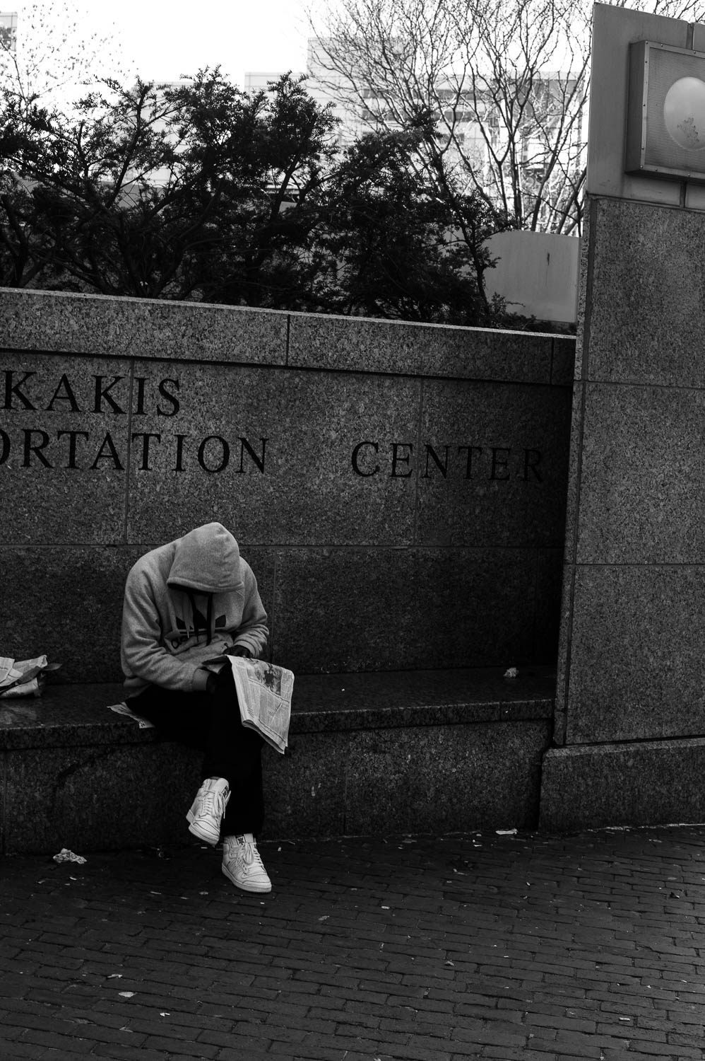 A man wearing a hood slumps over a newspaper in Boston