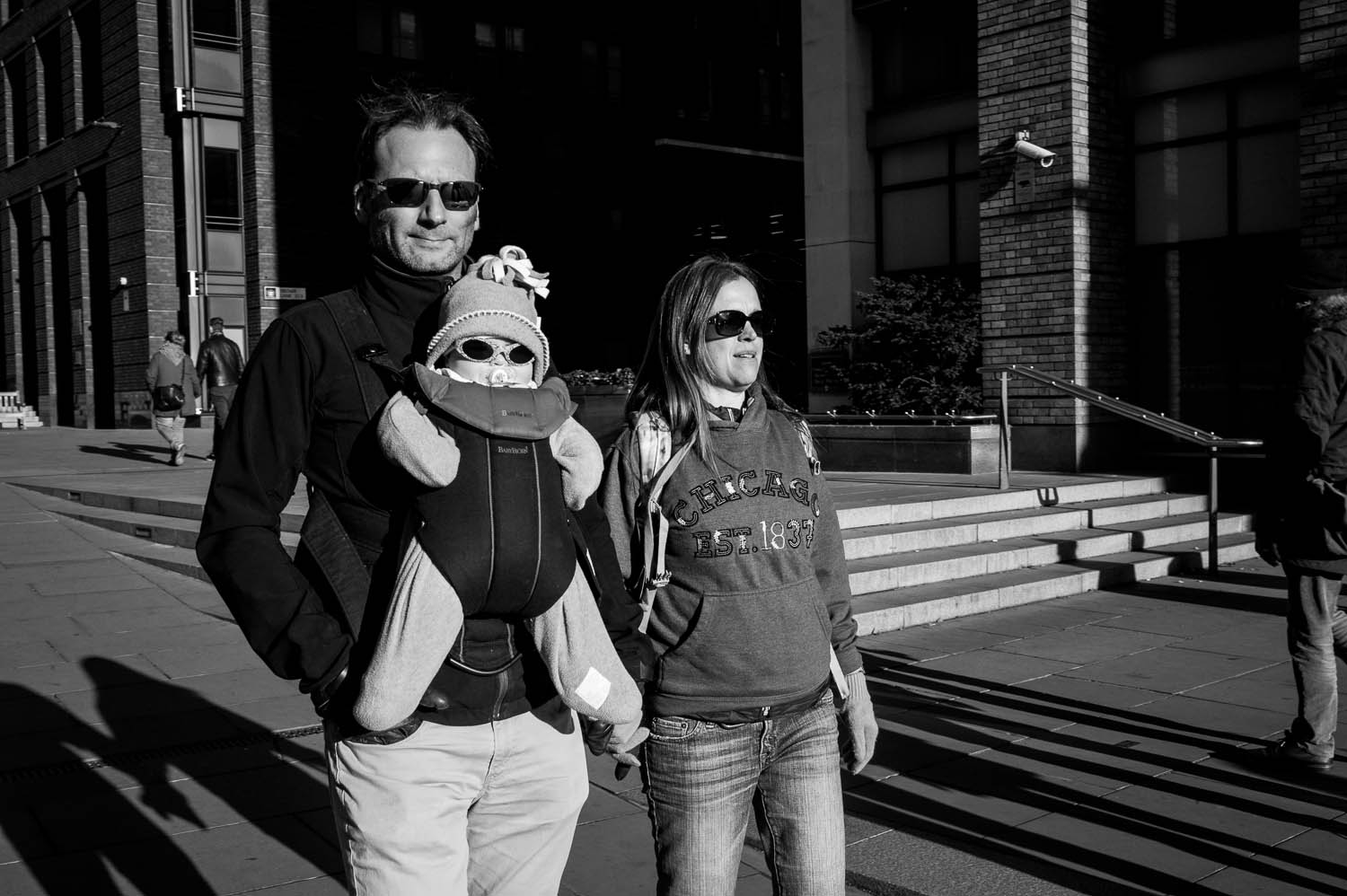 A couple with a baby carrier walk through London, all three wearing sunglasses