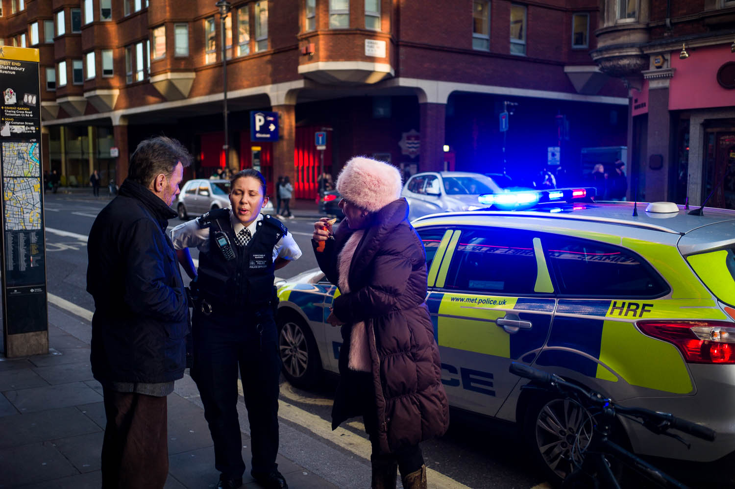 A London police officer chatting with a woman eating orange slices in a furry hat
