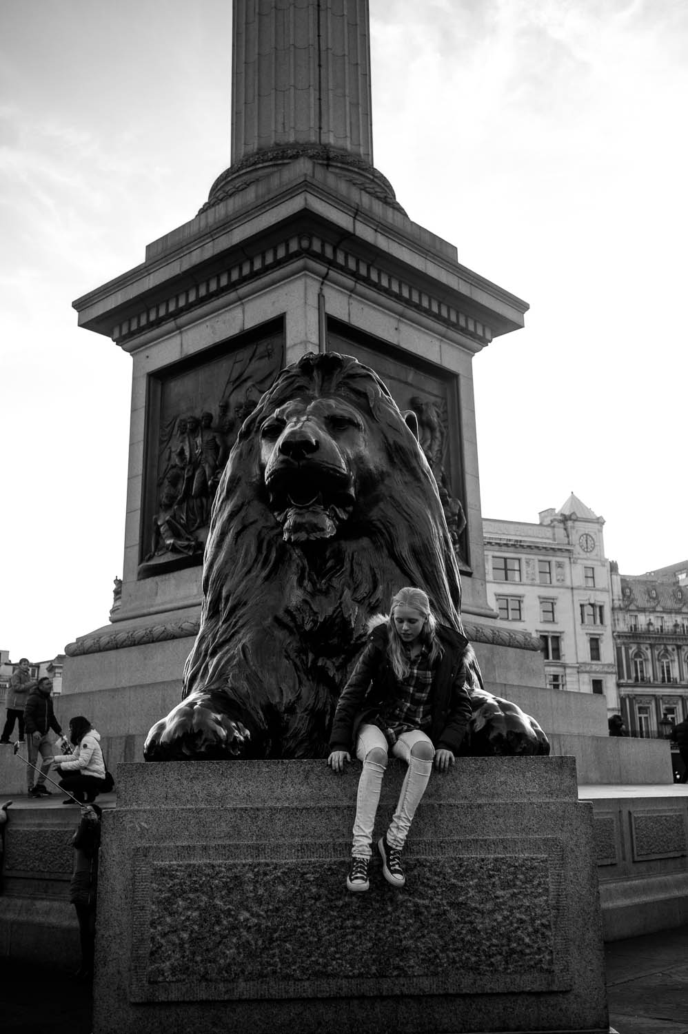A girl sites in front of a lion statue in London