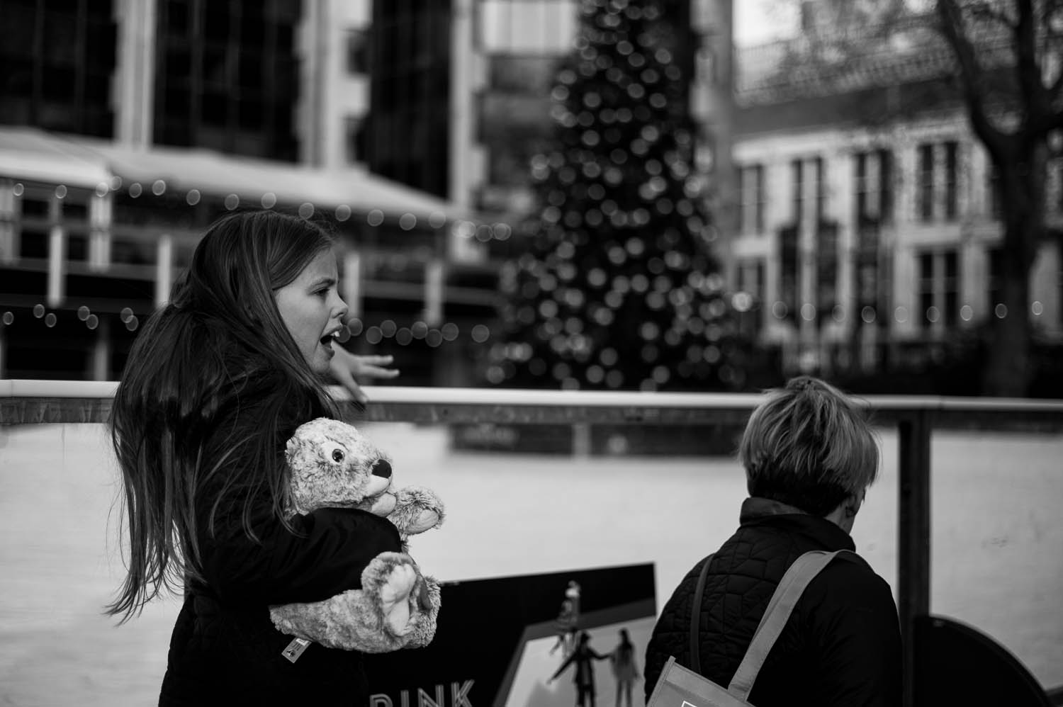 A small girl holding a stuffed animal in front of an outside ice rink and Christmas tree in London