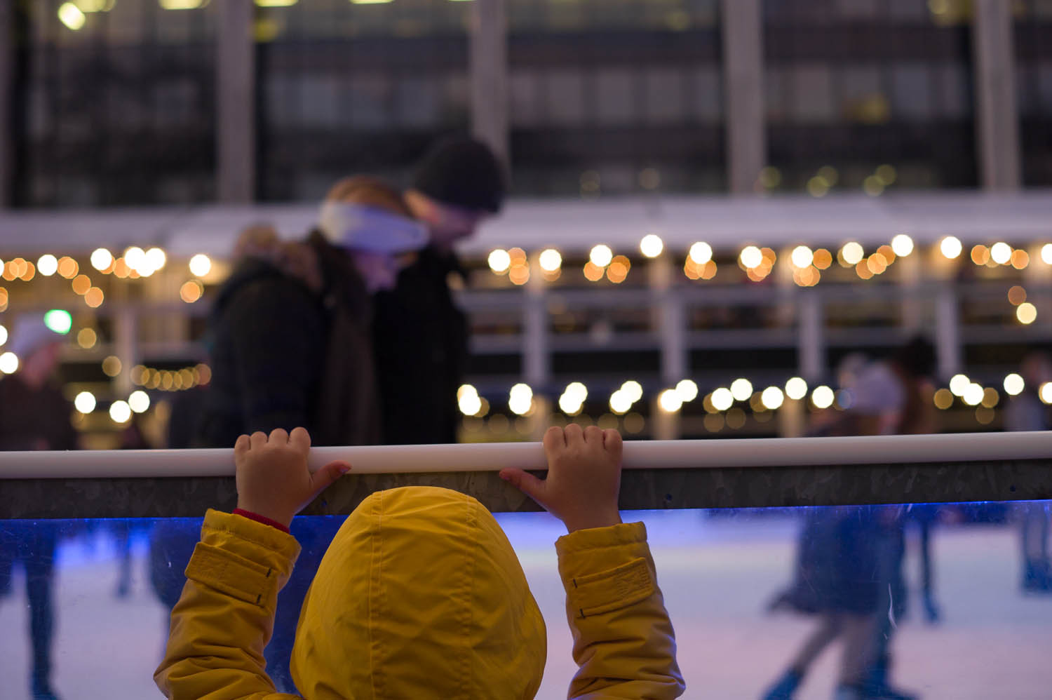 A child in a yellow jacket peers over the rail of an outside skating rink in London