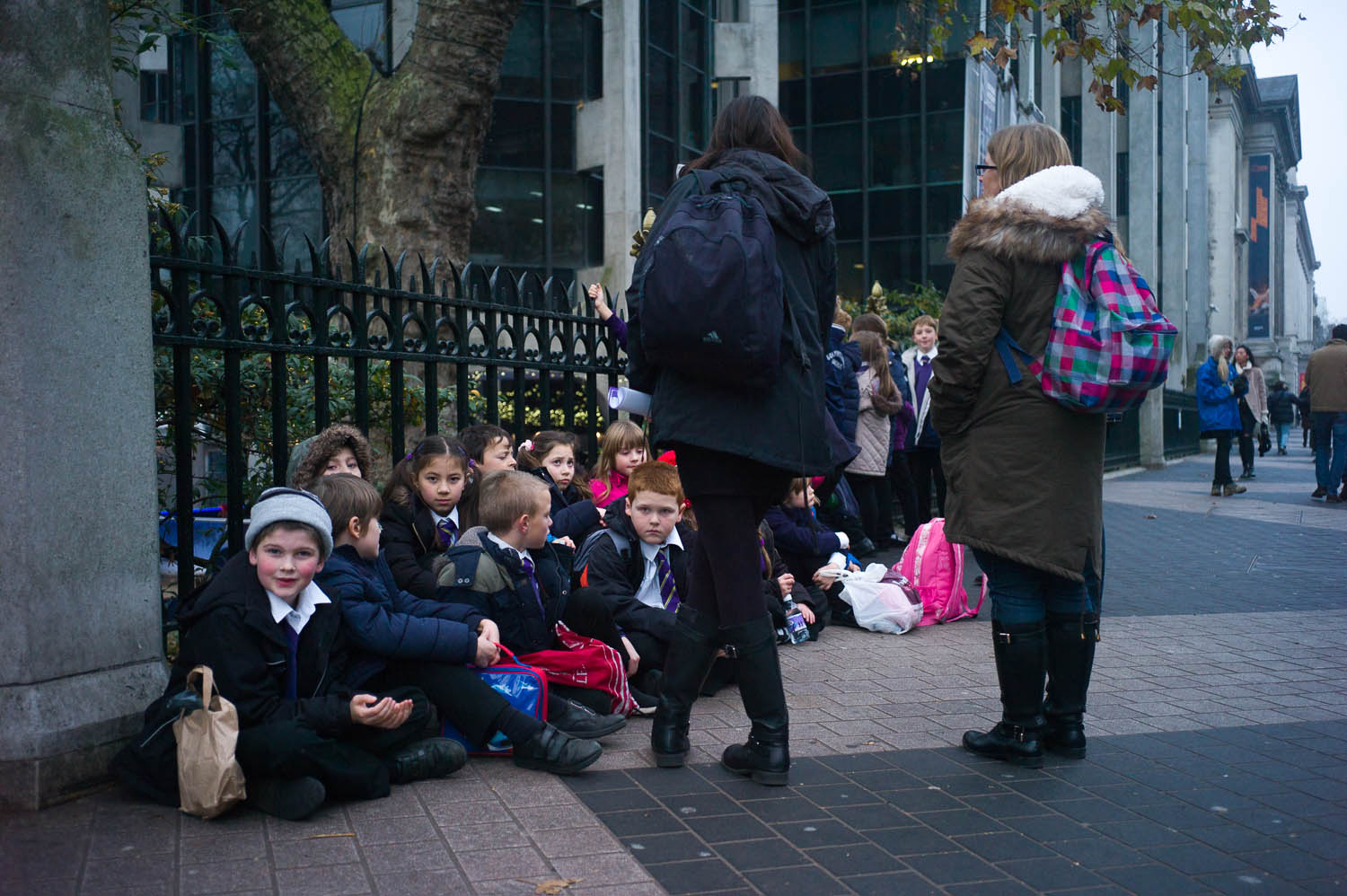Schoolchildren are seated against a fence near the museums in London