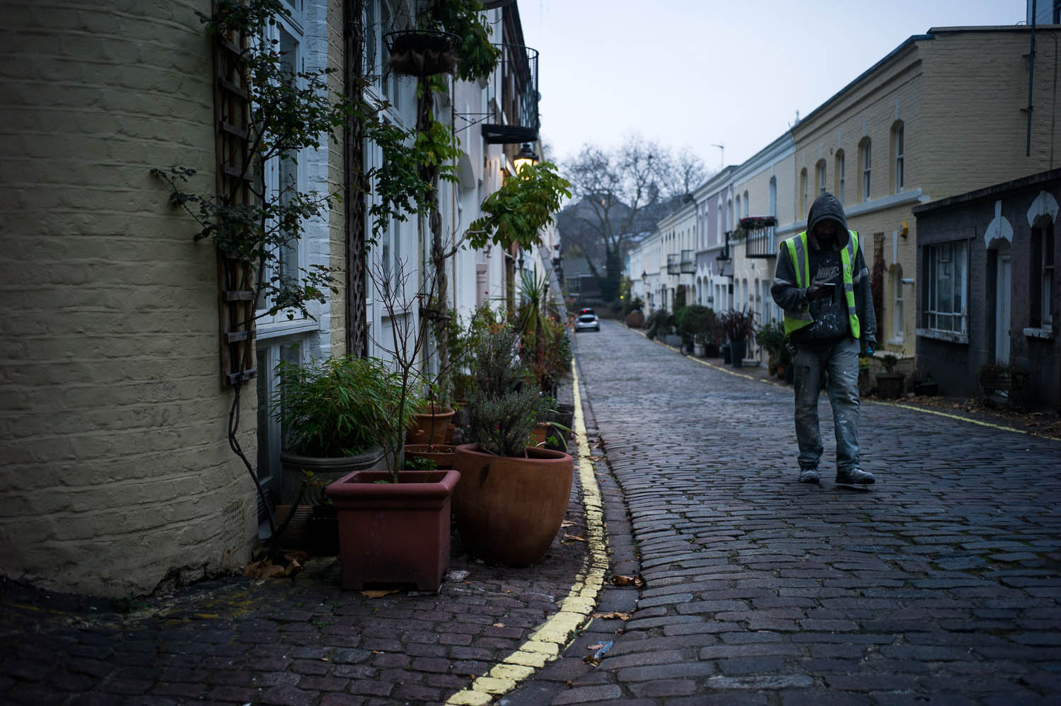A worker in a reflective vest walks through a cobblestone street in London