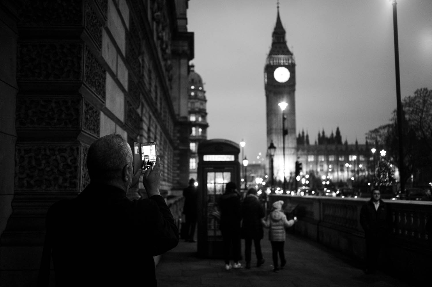 A man photographs Elizabeth Tower with his cell phone in London