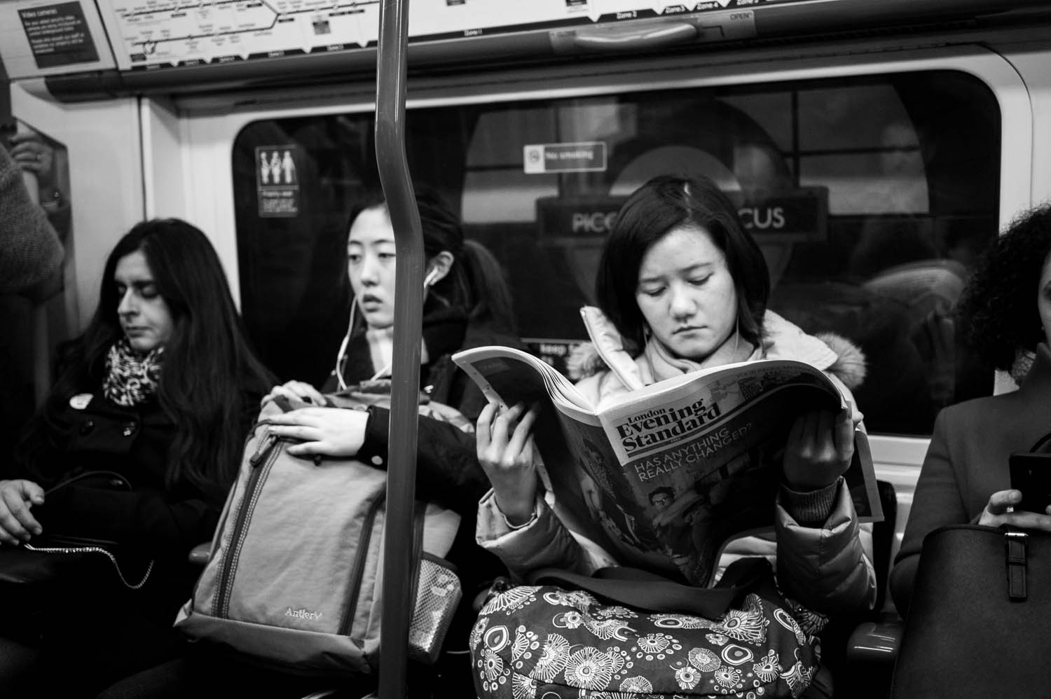 A woman reads the London Evening Standard on the London tube.