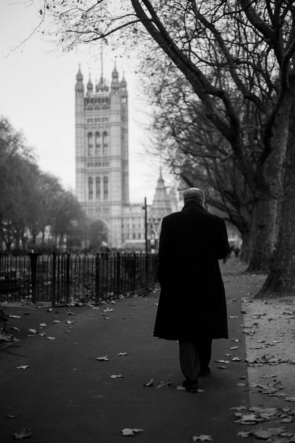 A man in a long coat walks along a path near the thames