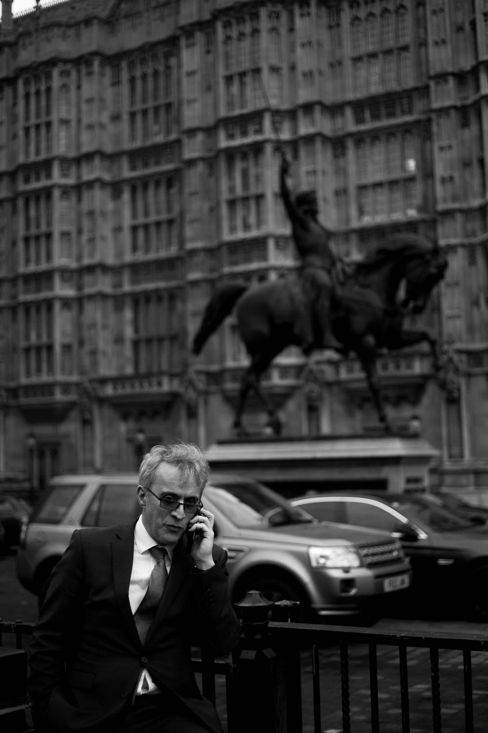 A man in a suit speaking on the phone in front of a horse statue in London