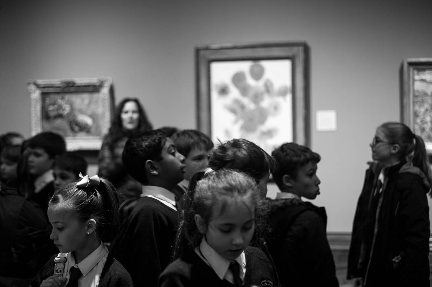 School children gathering around Van Gogh's Sunflowers in London.
