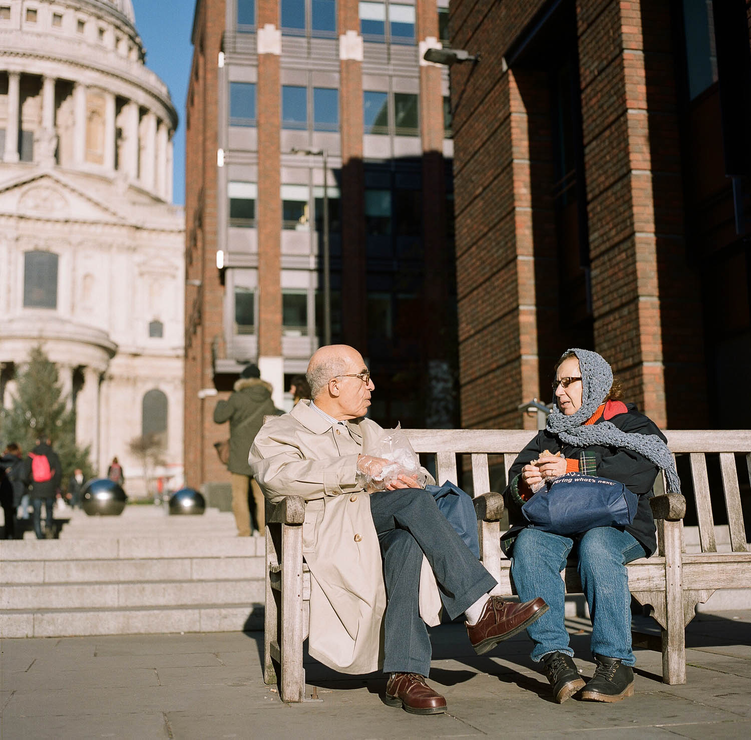A couple sitting on a bench in front of St. Paul's Cathedral