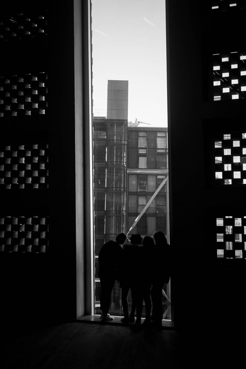 A group of children look through a tall window at the Tate Modern museum.
