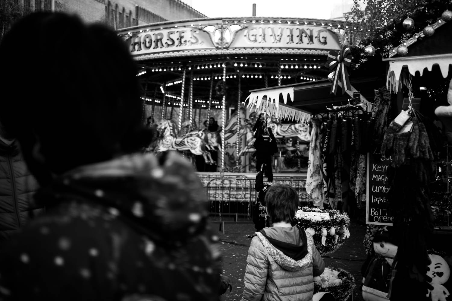 A child walks toward a spinning carousel in London