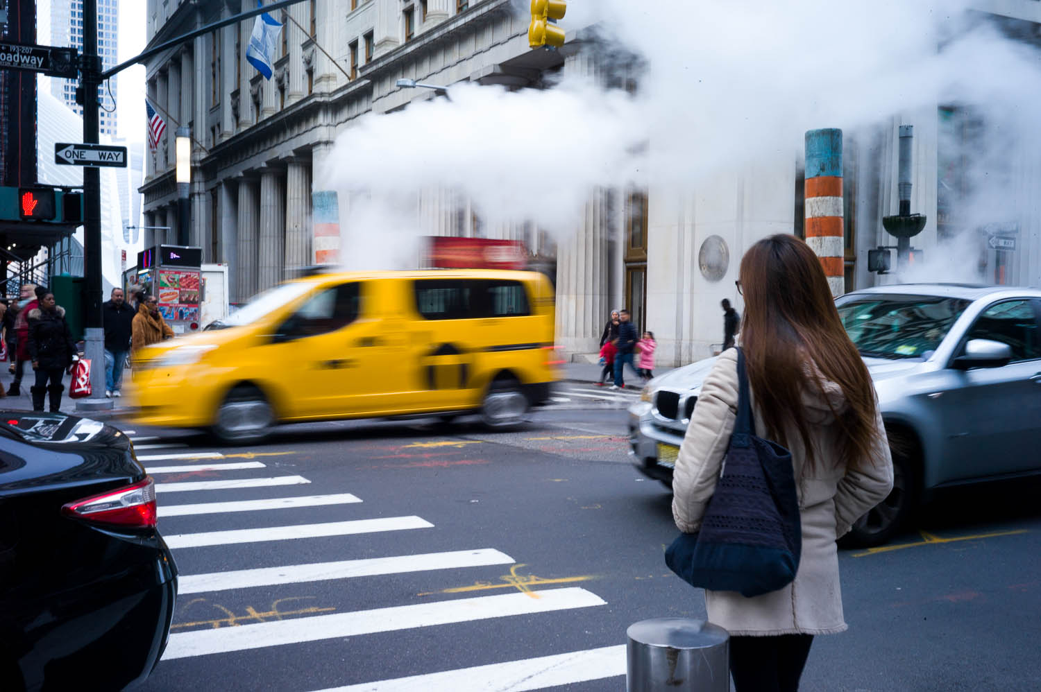 A girl stands at a NYC crosswalk as a yellow cab drives through