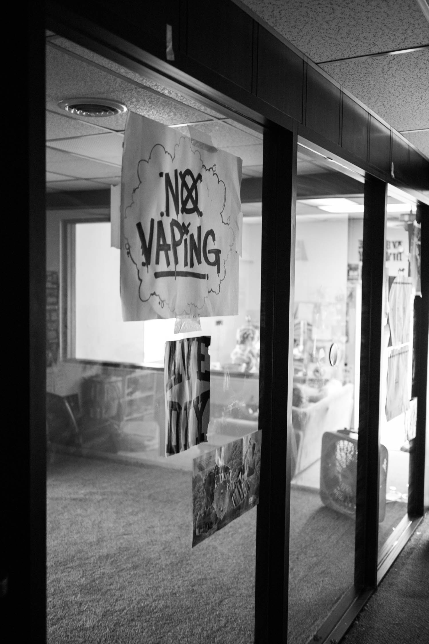 "A ""No Vaping' sign taped to a window at Ave DIY"