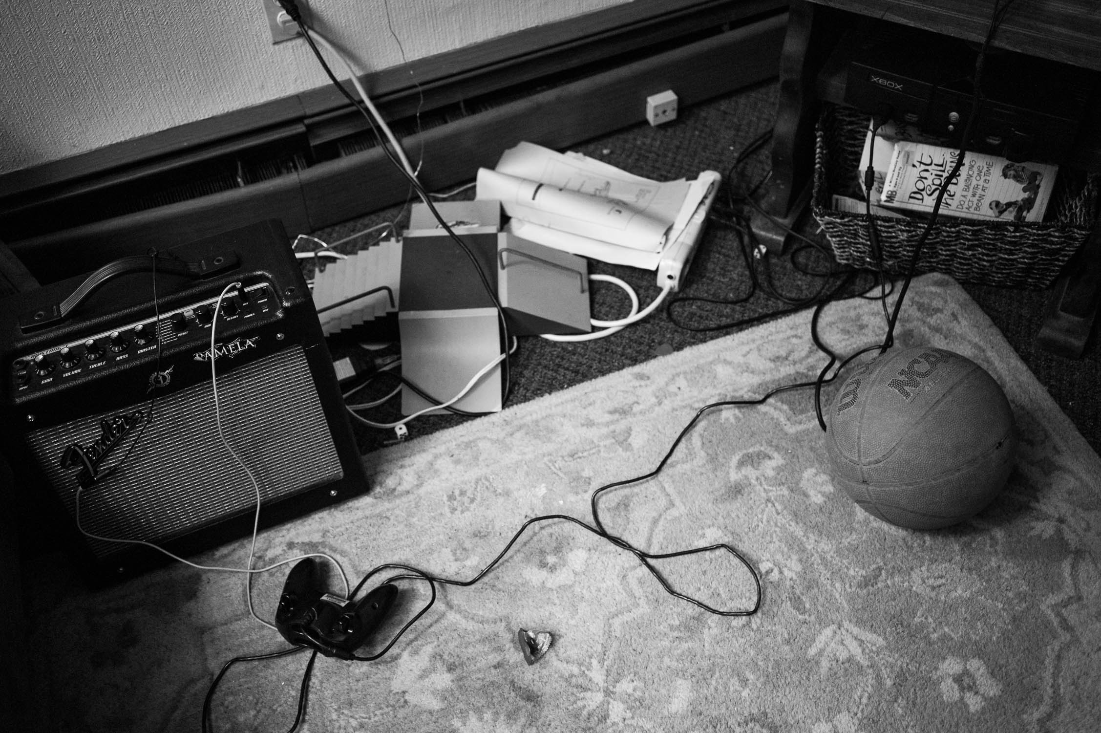 A practice amp, xbox controller, and tech deck skate park on the floor of Avenue D.I.Y.