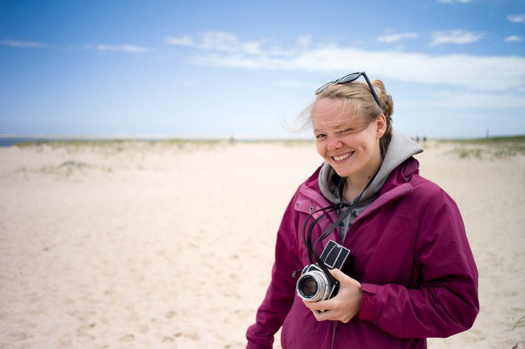 Amanda Vogler holding a Hasselblad 500C on the beach for NEWLK in Nantucket
