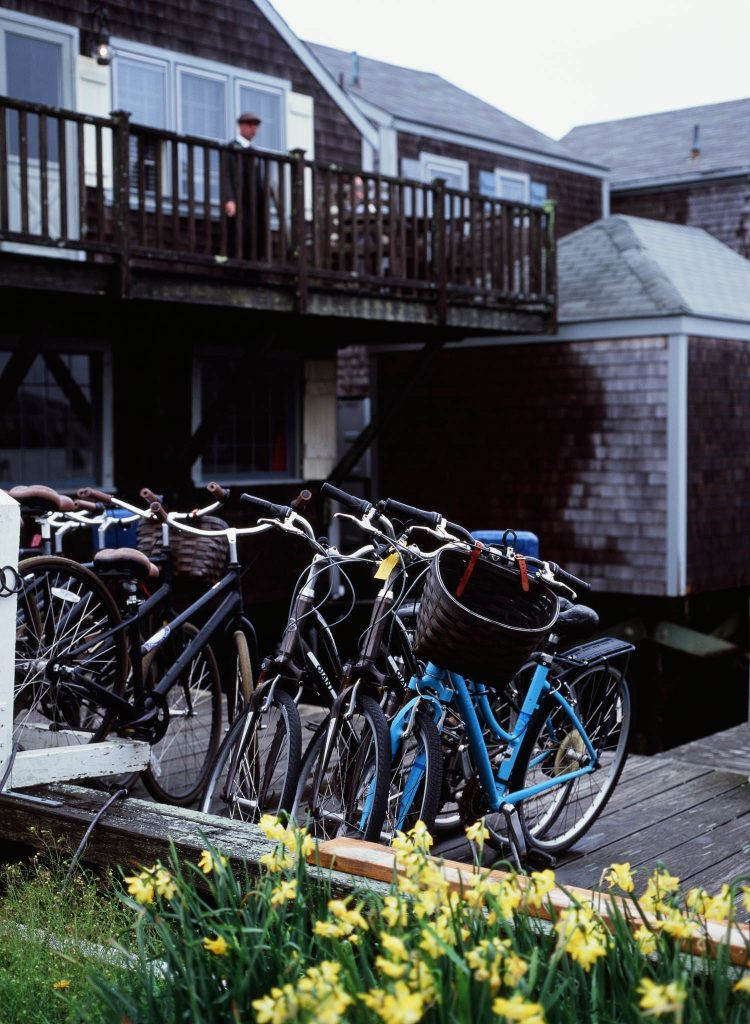 A man overlooking a row of bicycles from a balcony in Nantucket