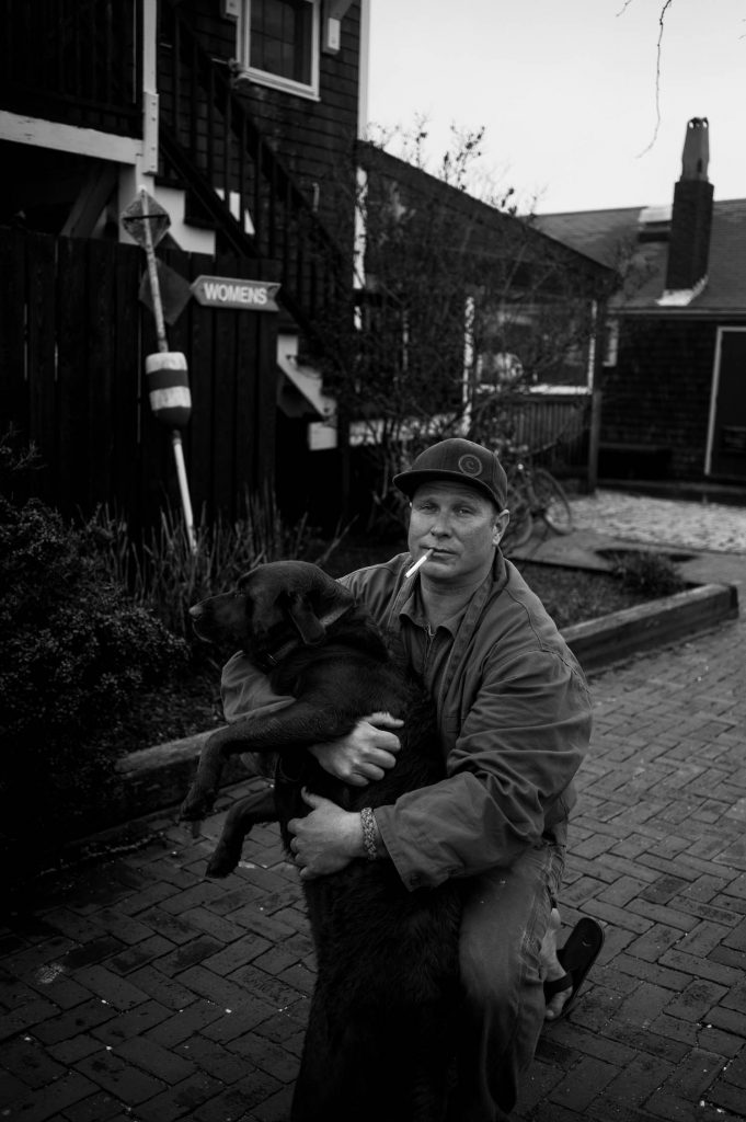 A man with a cigarette in his lips holding his dog for a portrait.